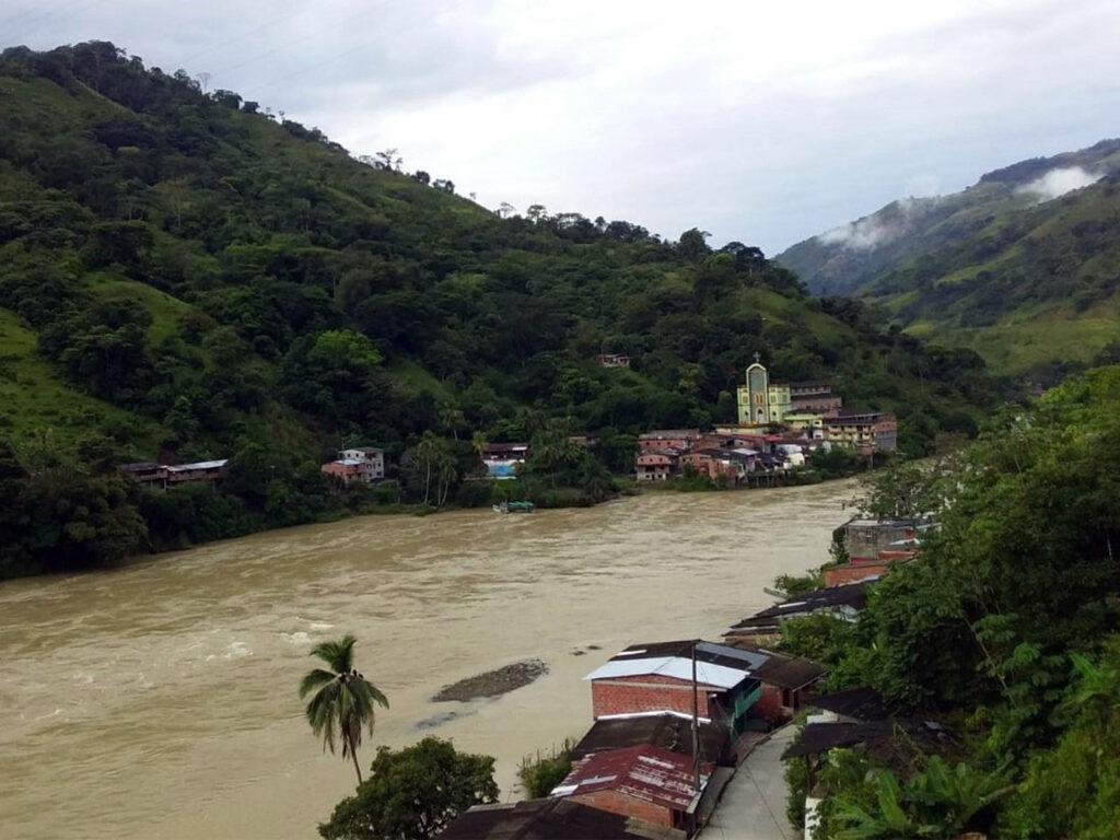 Flod omgiven av trädbeklädda berg