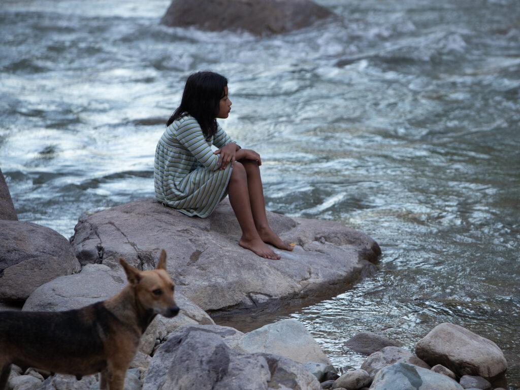 Flicka sitter vid förorenad flod