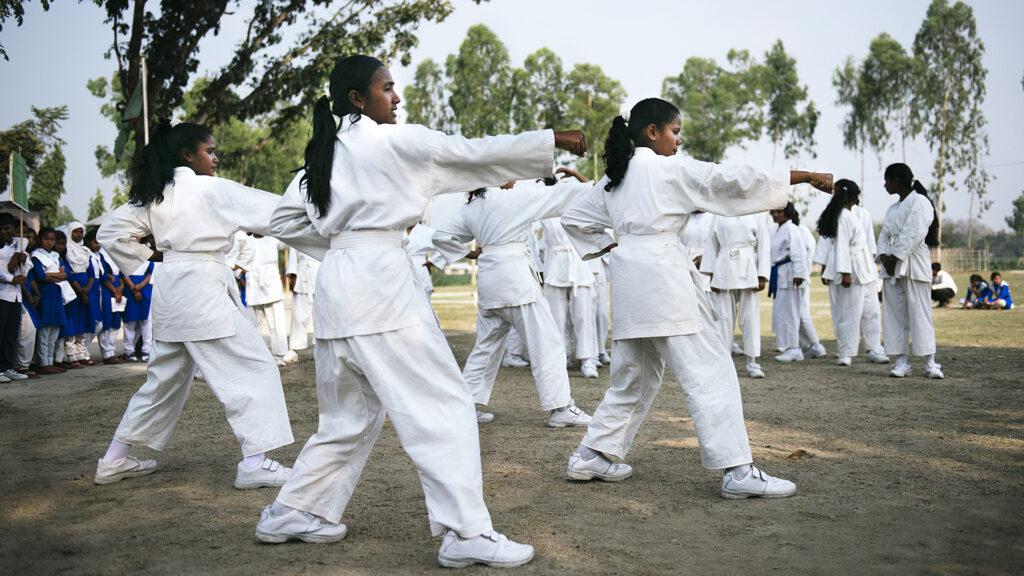 En grupp med unga tjejer som tränar karate utomhus. De har vita karatedräkter på sig. I bakgrunden syns träd och en annan grupp tjejer som tittar på.