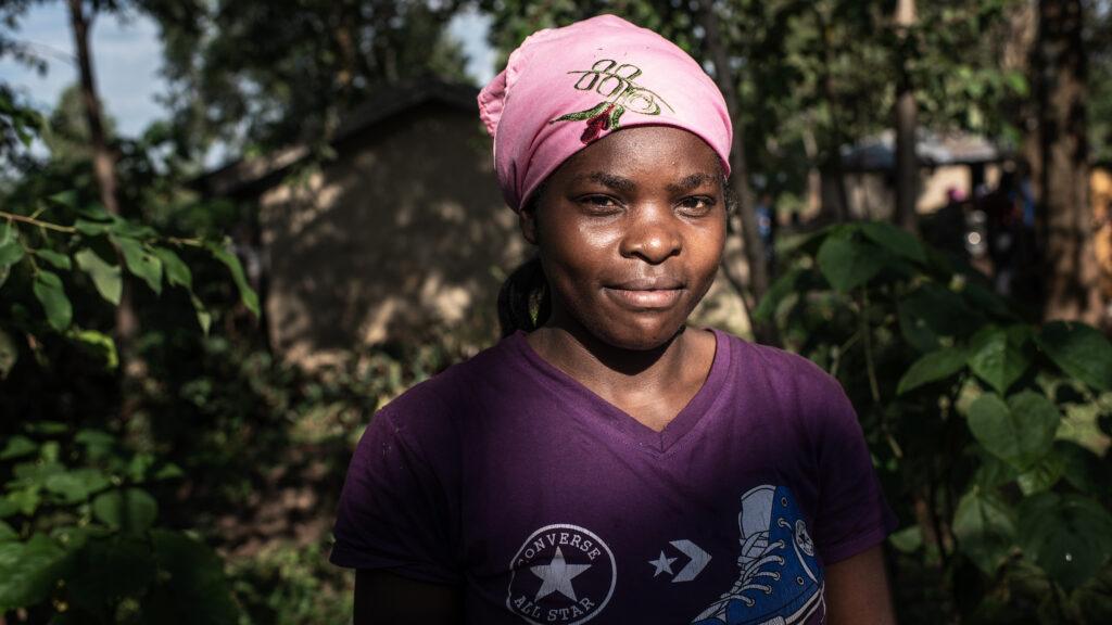 Kvinna står framför träd och buskar. Hon har en rosa sjal på huvudet.