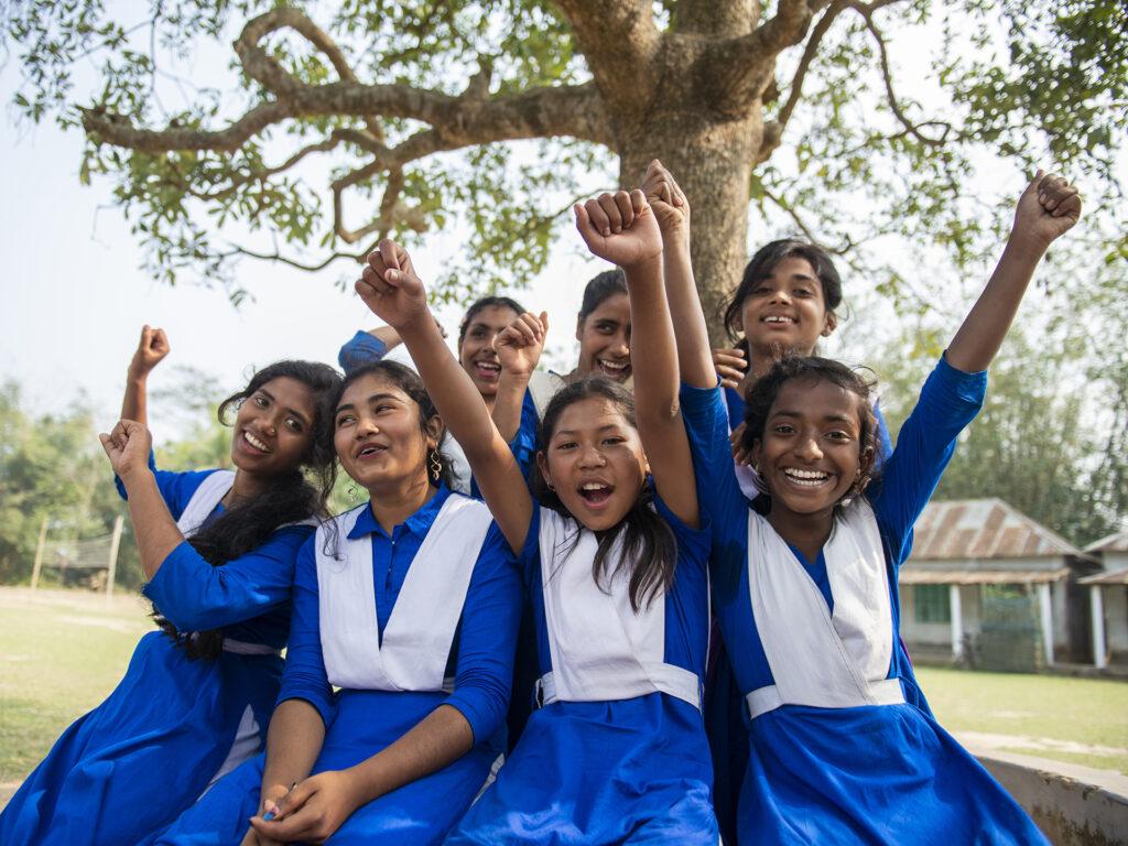En grupp av leende och skrattande flickor sitter intill ett träd. De är klädda i likadana blåa skoluniformer och sträcker upp händerna i luften.