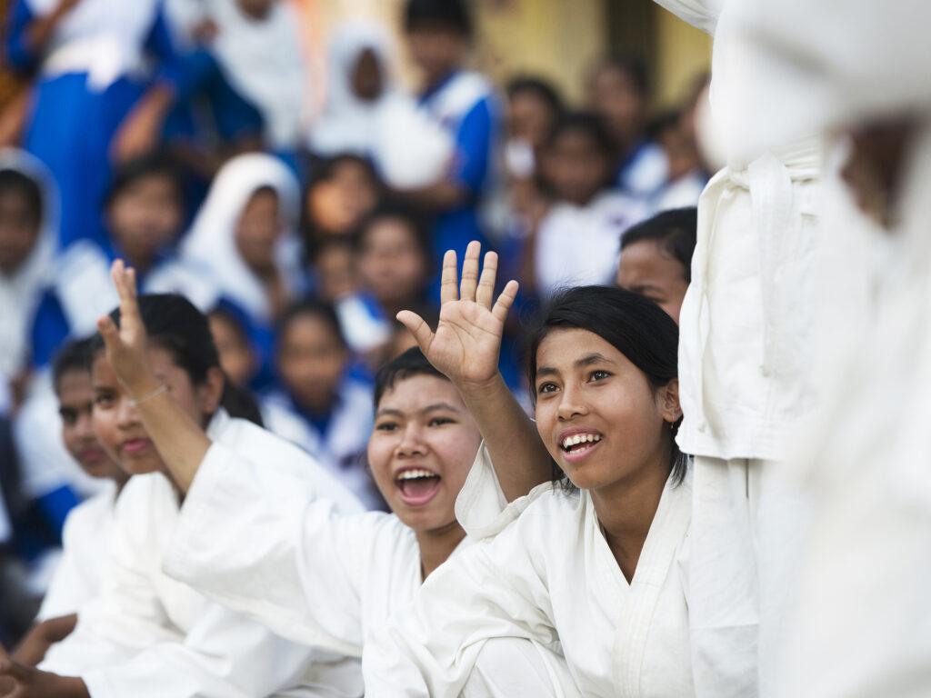 En stor samling med flickor, de längst fram har karatedräkter på sig. En av dom har händerna i luften.