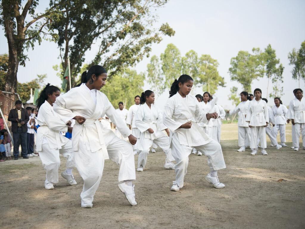 Ett stort antal flickor i vita karatedräkter står utomhus och tränar karate. Bakom dom syns träd och flera personer som tittar på.