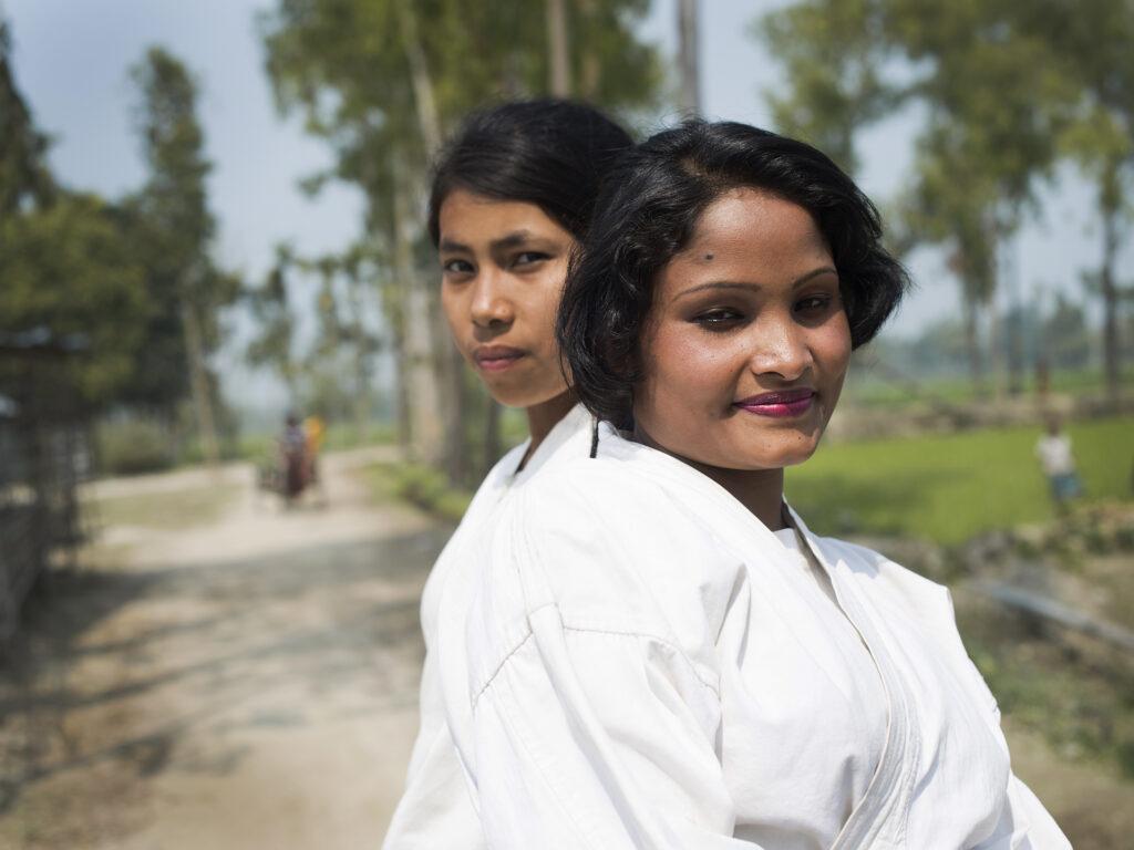 Två kvinnor står rygg mot rygg i vita karatedräkter och ser in i kameran. Bakom dem syns en landsväg och grönområden.