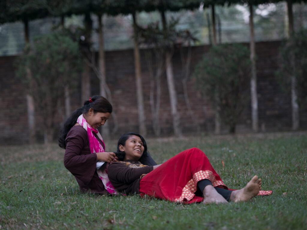 Systrarna Akhi och Sharifa på en gräsmatta