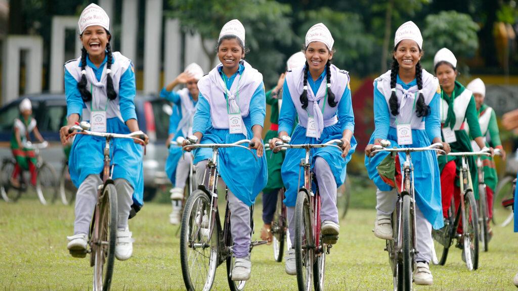 Fyra glada flickor på cykel