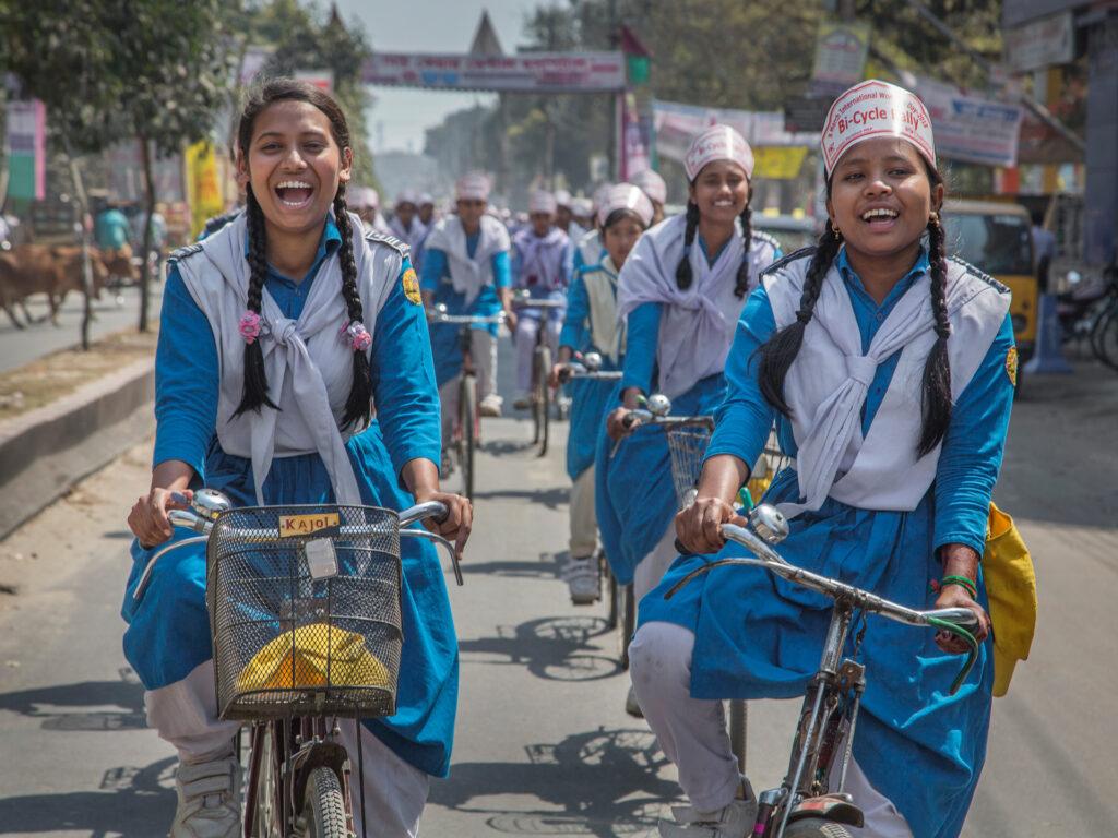 Flickor cyklar i en procession