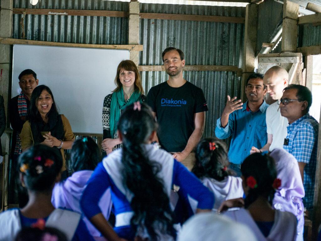 Personer framför en skolklass i Bangladesh