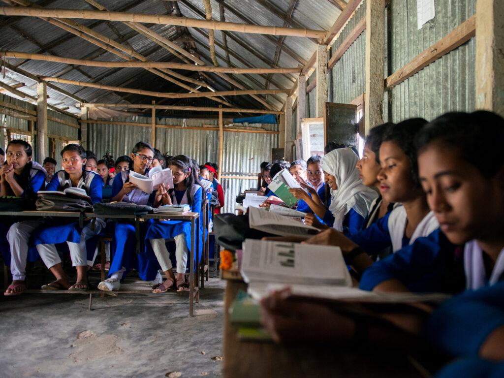 Skolungdomar i ett klassrum av stolpar och plåt