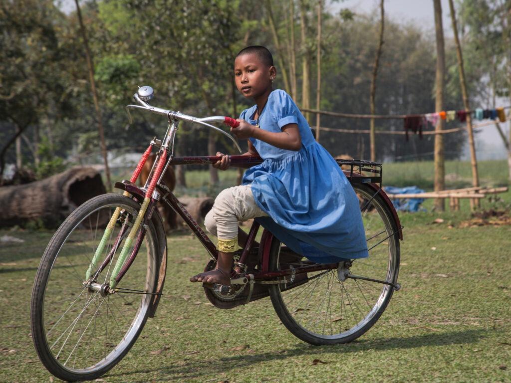 En liten flicka cyklar på en stor cykel