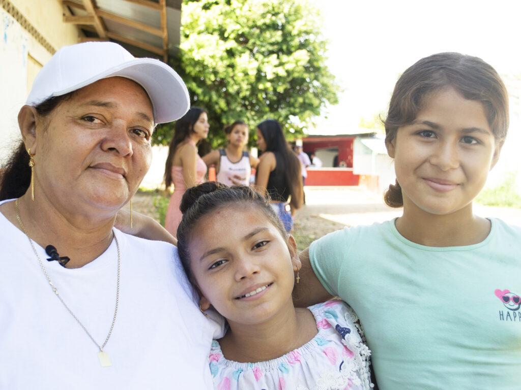 En kvinna i keps står med armen om två barn. I bakgrunden syns fler barn och ungdomar och en skolbyggnad.