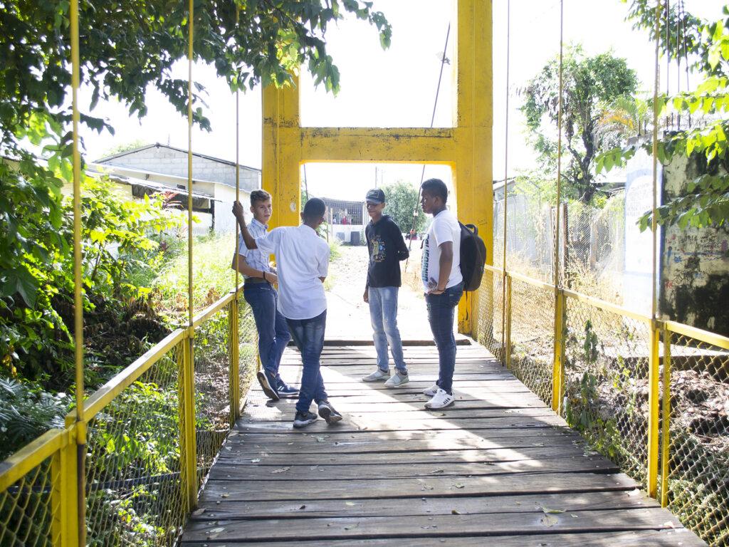 Fyra ungdomar står vid slutet av en gul bro. Bakom bron syns olika byggnader.