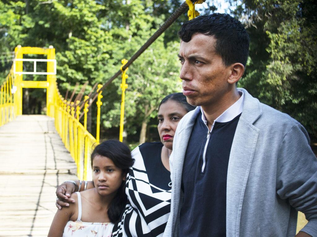 Man står med barn och kvinna vid bro, skog syns i bakgrunden