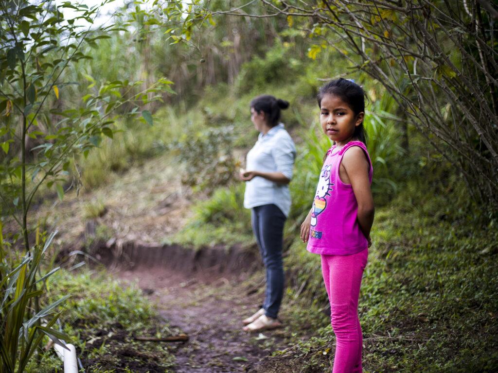 Ett barn står längst fram i bilden och tittar mot kameran, på en skogsstig. Bakom barnet står en kvinna.
