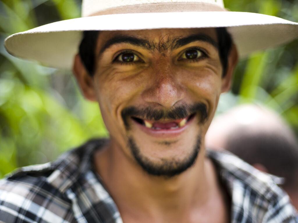 Närbild av en man med ljus hatt och stort leende. Mannen saknar framtänder.