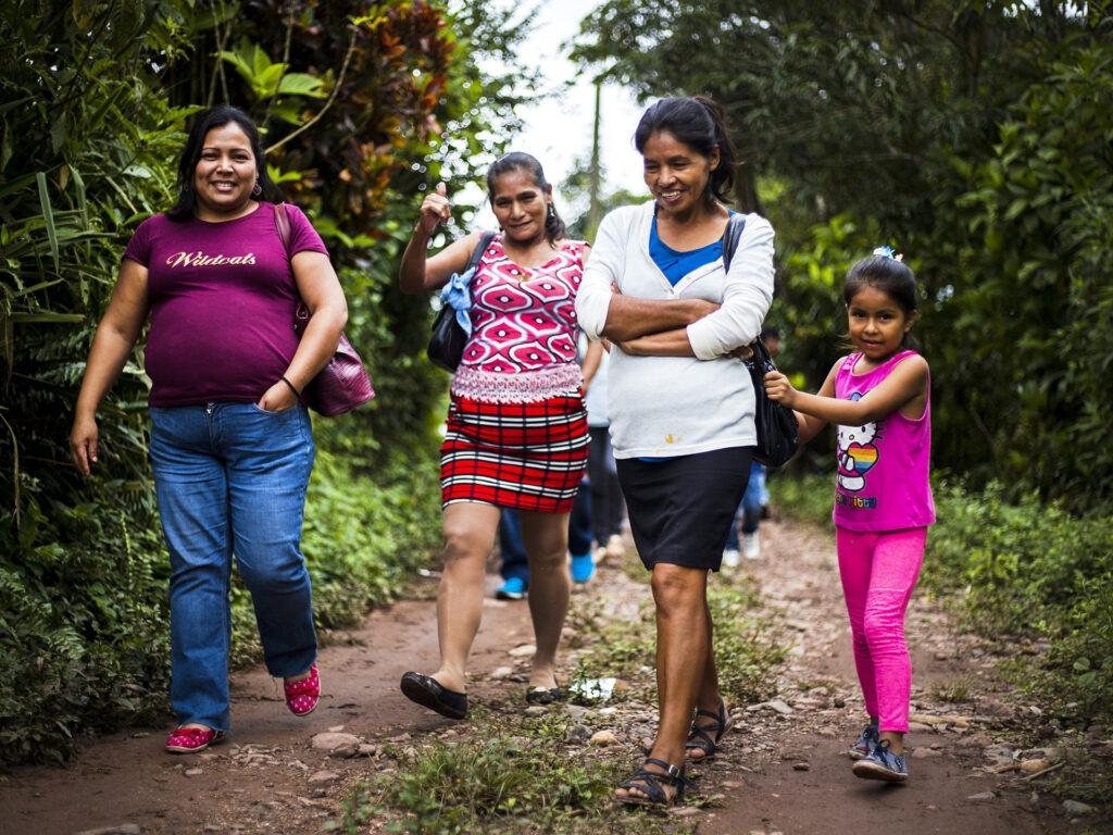 Tre kvinnor och ett barn vandrar på en bred stig i ett skogsområde. De ser glada ut.