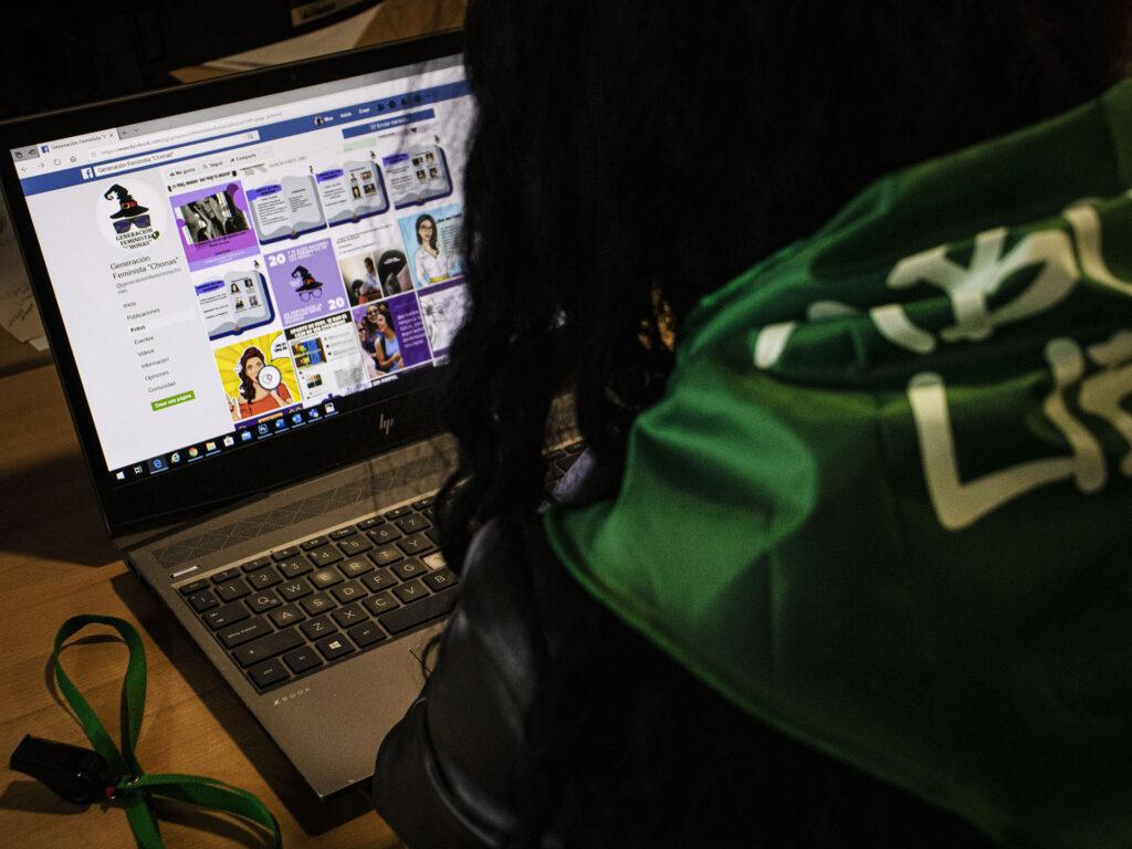En kvinna sitter i ett mörkt rum med ryggen mot kameran framför en dator. På skärmen syns en Facebook-sida med olika bilder.