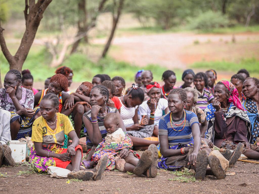 En grupp människor sitter under ett träd