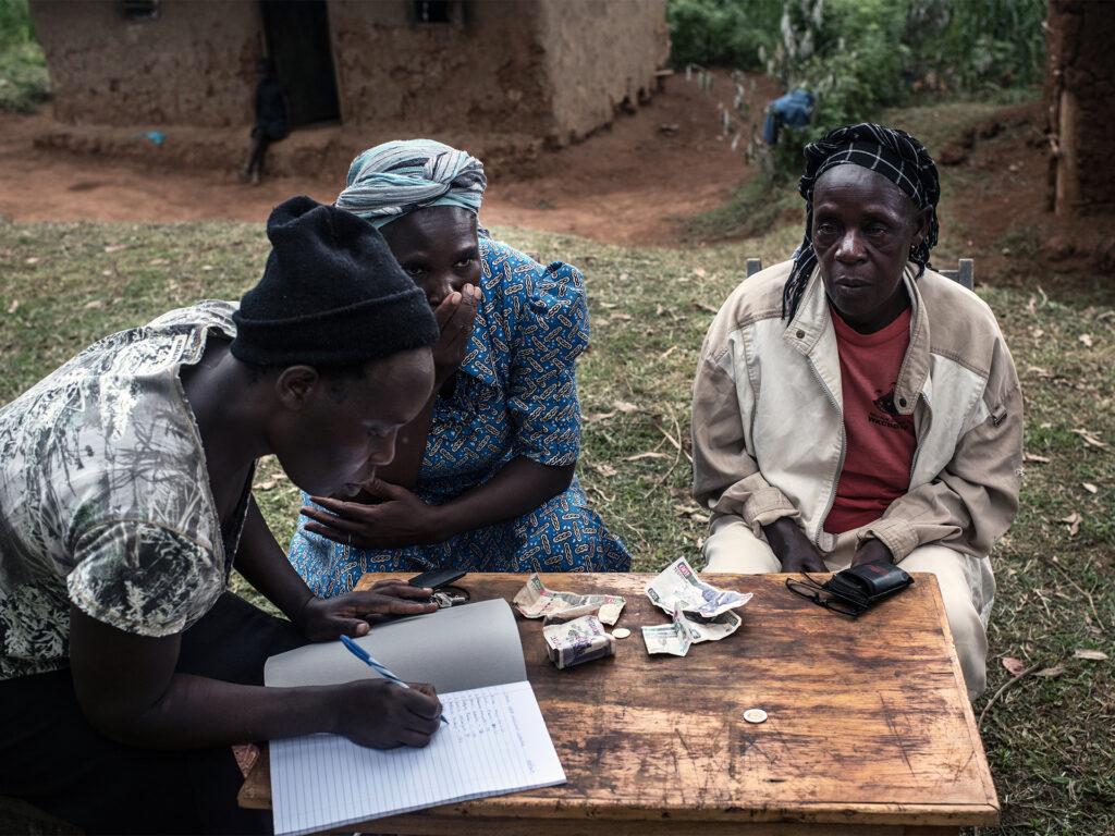 Tre kvinnor sitter vid bord och bokför pengar de lånar till varandra.