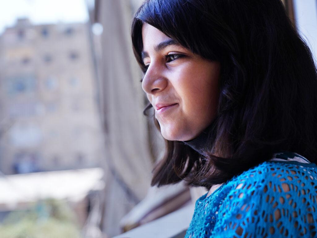En flicka ser ut genom ett fönster. I bakgrunden syns höga byggnader.