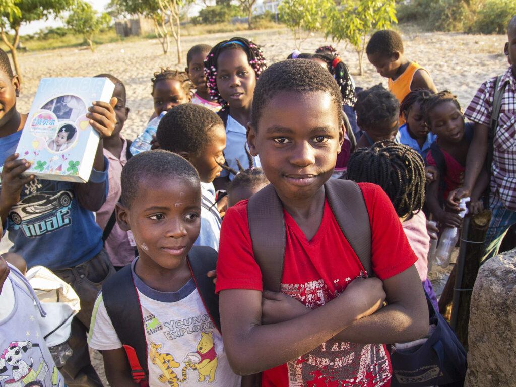 En grupp med barn med skolväskor på ryggen står utomhus.
