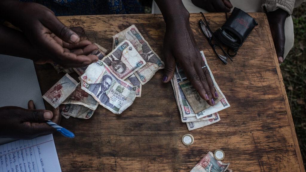 Sedlar och mynt ligger på ett bord, händer sträcker sig efter pengarna.