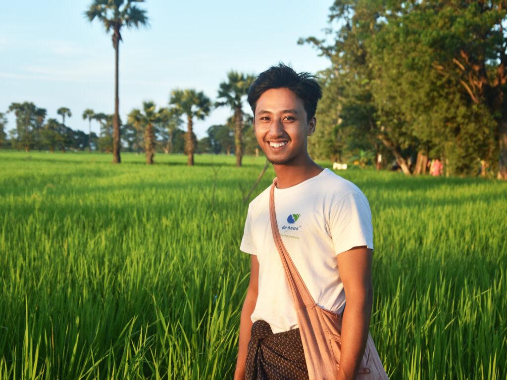 En ung man står i ett öppet grönt fält.
