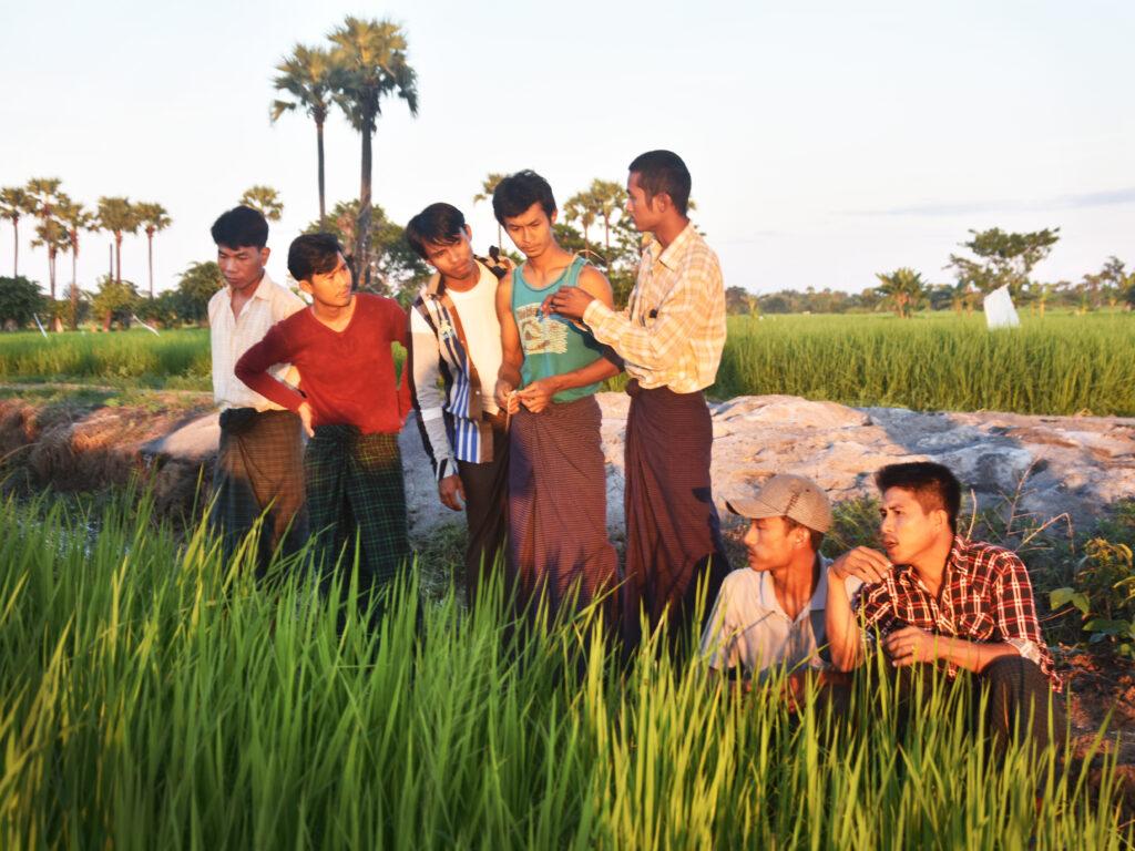 En grupp av unga män står i ett grönt fält med högt gräs och träd i bakgrunden. De har solen i ansiktet.