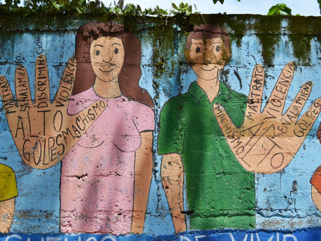 Bild av en muralmålning på en vägg. På målningen syns en kvinna och en man som håller upp sina händer. I händerna har de skrivit budskap på spanska mot våld.