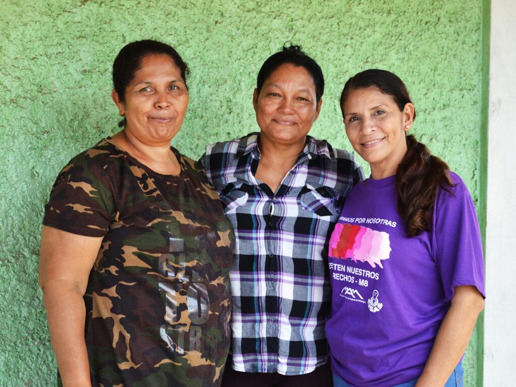 Tre leende kvinnor står mot en grön vägg och håller armarna om varandra.