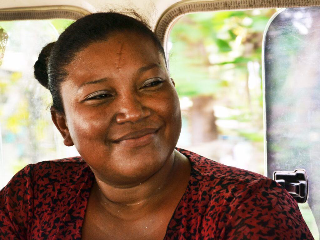 Närbild av en kvinna som sitter i en bil eller buss. Hon har rödmönstrad blus och ler.