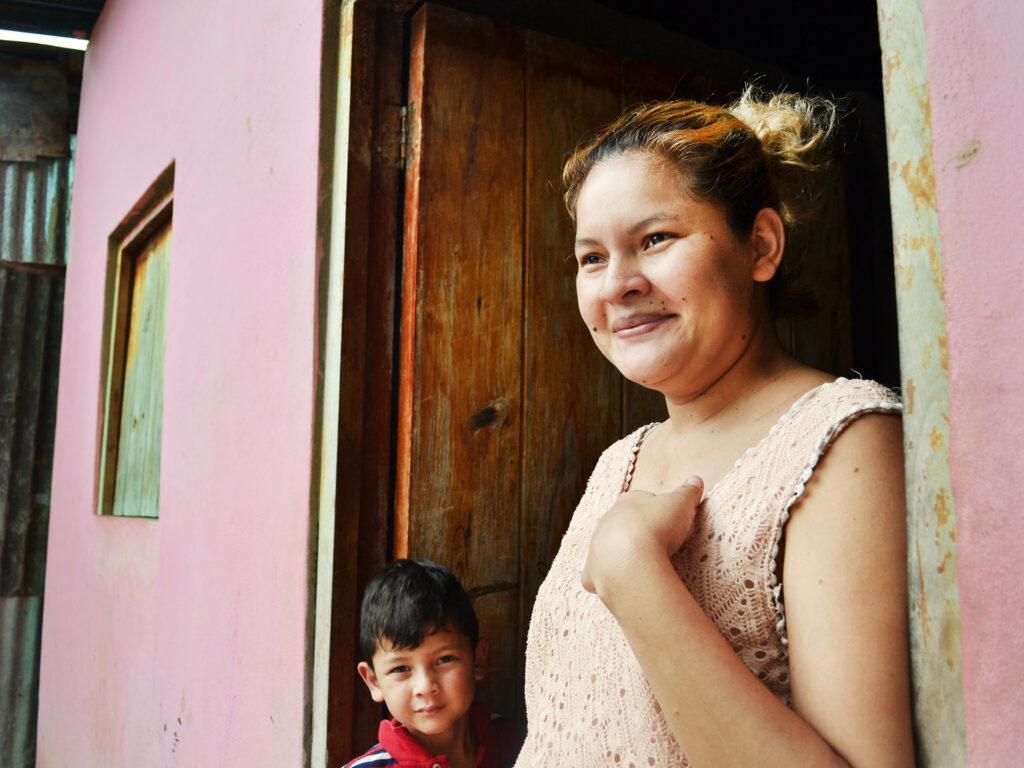 En leende kvinna står i dörröppningen till ett rosa hus. Bredvid henne står ett barn.
