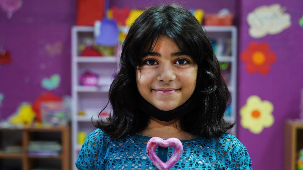 En leende flicka ser in i kameran. I bakgrunden syns lila väggar med målade blommor, leksaker och en bokhylla.