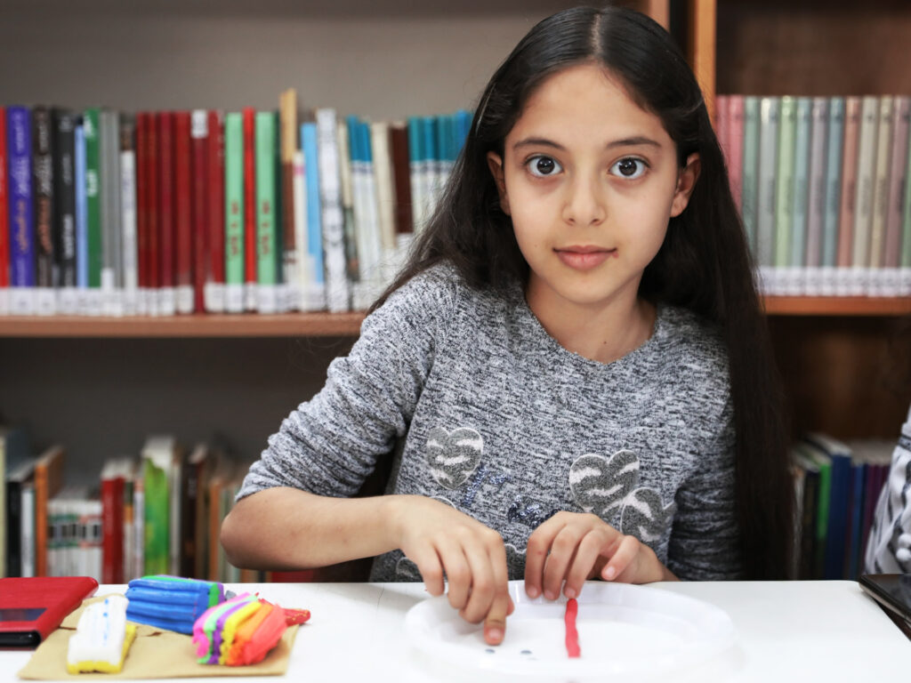 Flicka sitter i ett bibliotek, framför sig har hon modellera i olika färg som hon jobbar med.