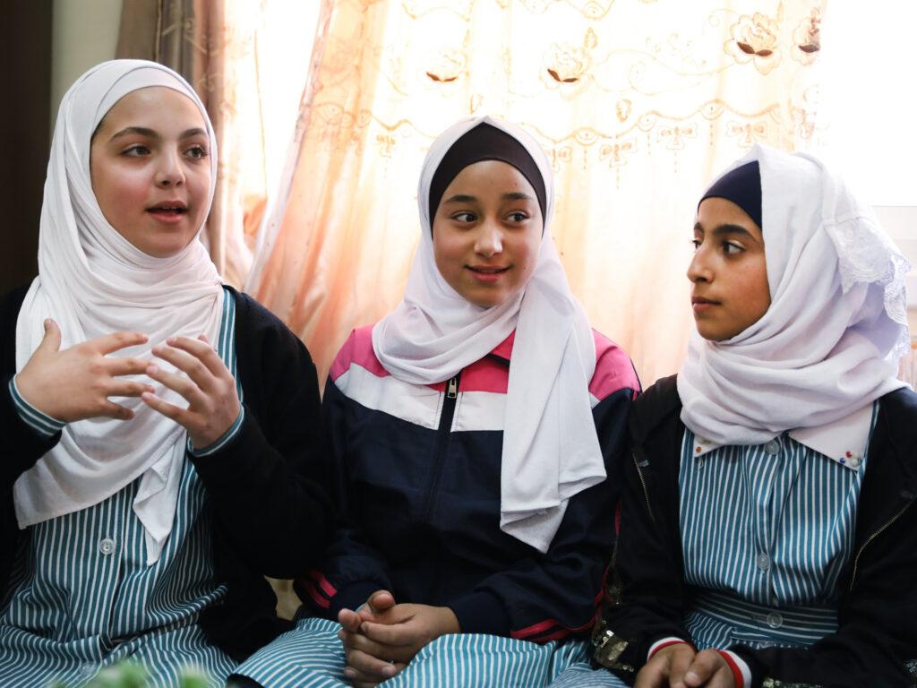 Tre unga flickor i hijab pratar och gestikulerar. Bakom dem syns ett fönster med en spetsgardin.