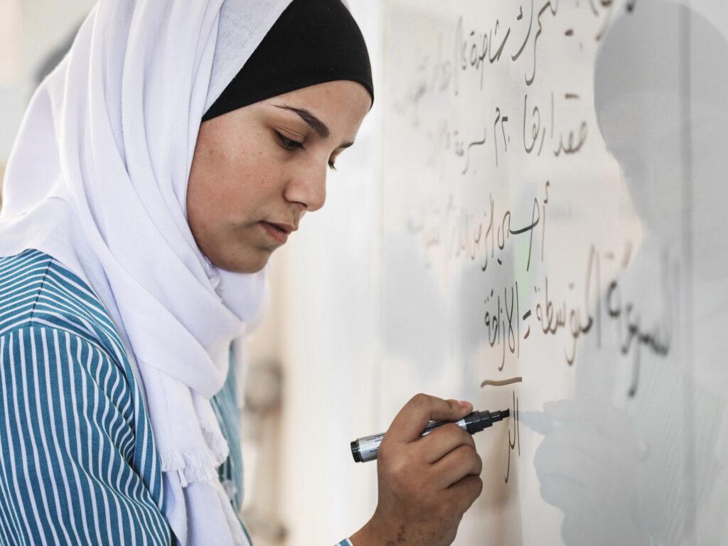 En kvinna i vit hijab skriver med svart penna på en whiteboard.