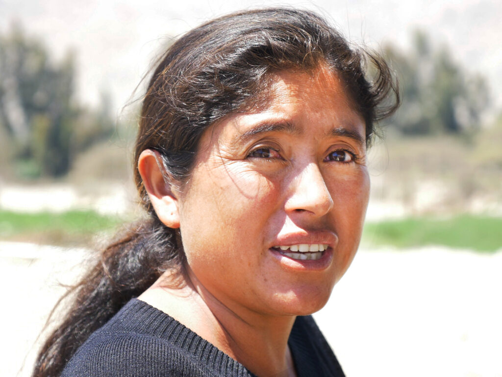 Närbild av kvinna som står i ett fält med odlingar.