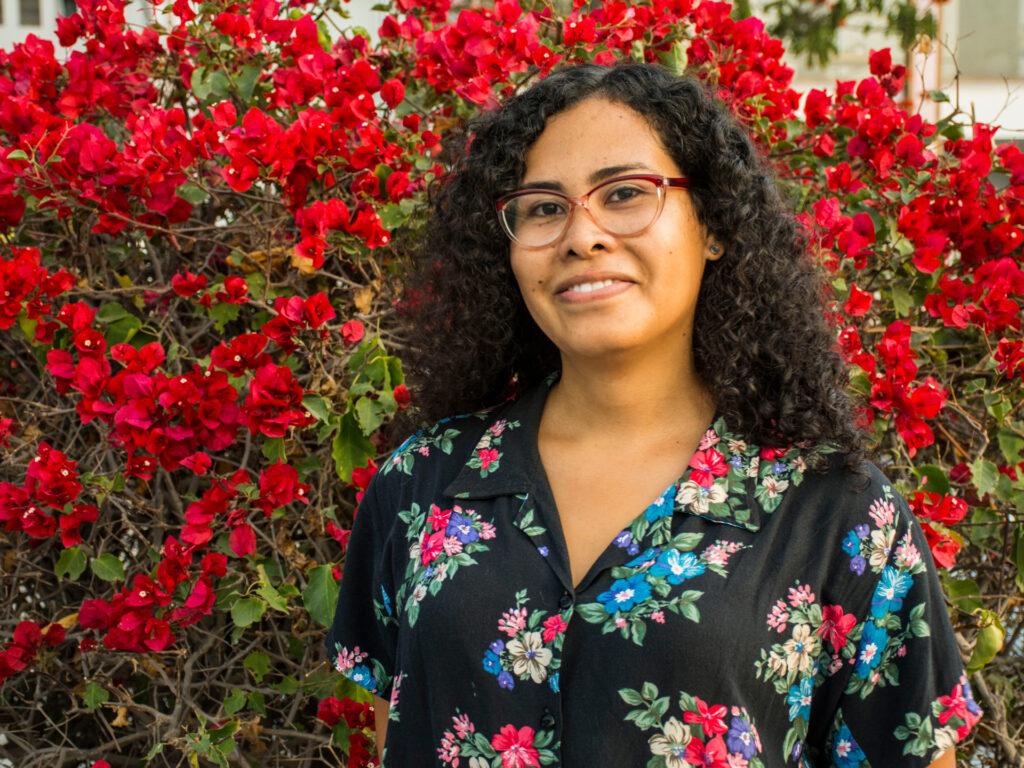 En kvinna framför en blommande buske