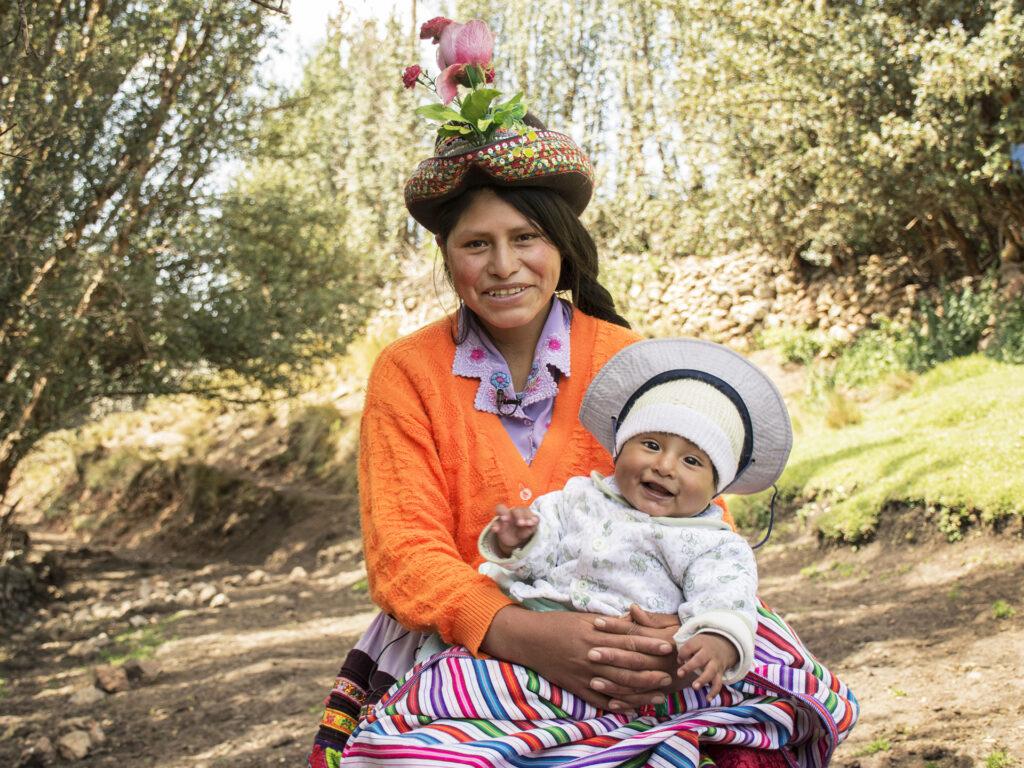 En leende kvinna sitter i ett grönområde med en bebis i famnen.