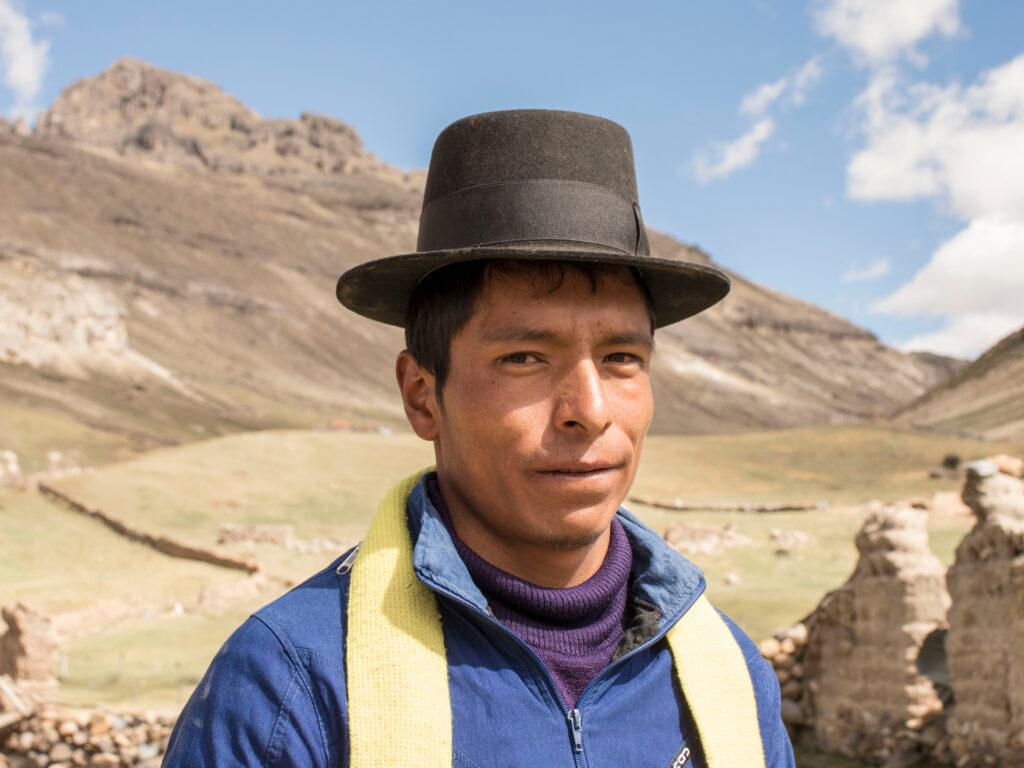 En man med hatt framför ett berg