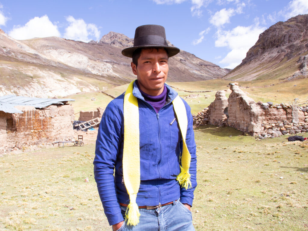 En man i hatt framför berg