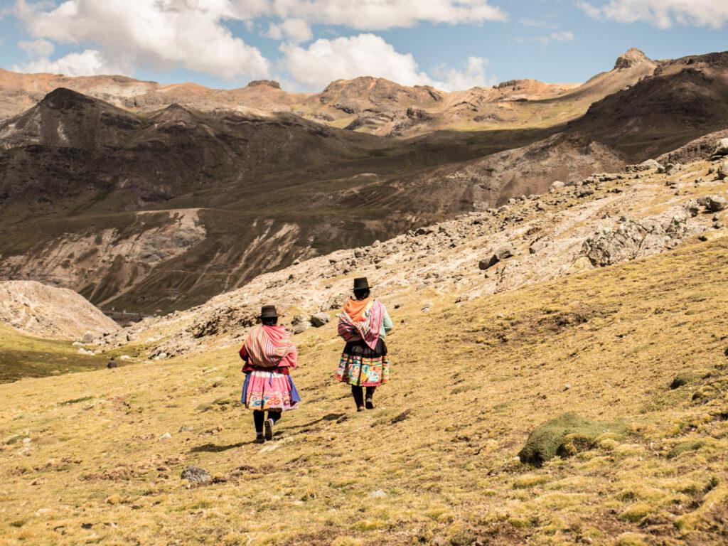 Två kvinnor går framför berg