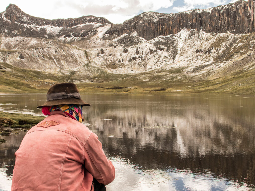 En man sitter framför en damm