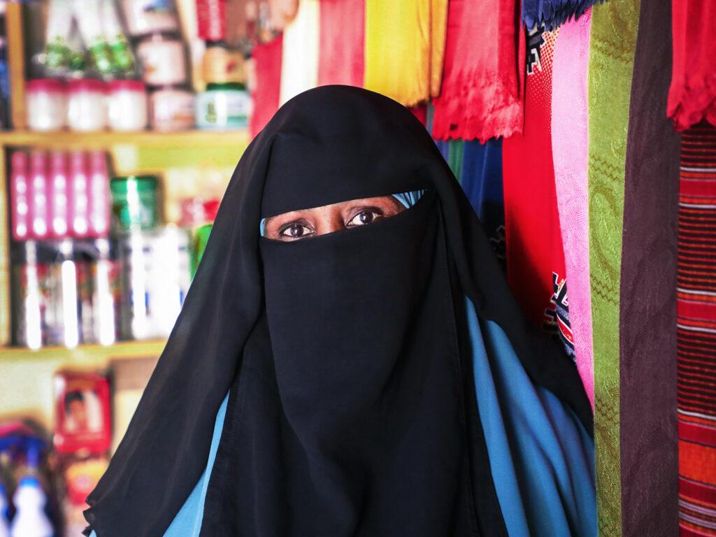 Närbild av kvinna i svart niqab och blå hiijab i en butik. I bakgrunden syns hyllor med livsmedelsprodukter och tyger i olika färger och mönster.