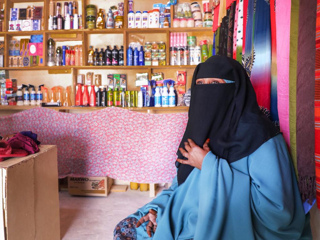 En kvinna i svart niqab och blå hiijab sitter på golvet i en butik. I bakgrunden syns hyllor med livsmedelsprodukter och tyger i olika färger och mönster.