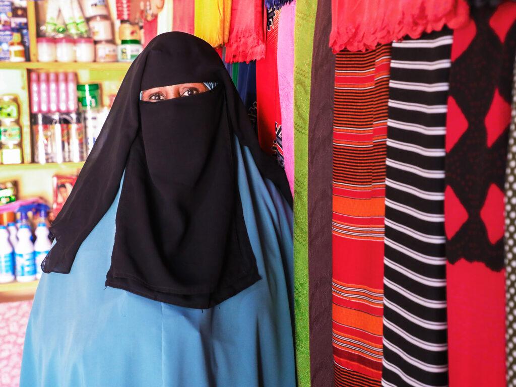Porträtt av kvinna som bär svart niqab med en blå hijab under. Hon står lutad mot en vägg där det hänger tyger i olika mönster och färger.