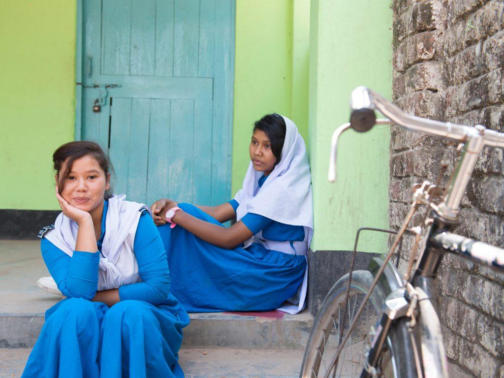 Två flickor sitter på en trappa