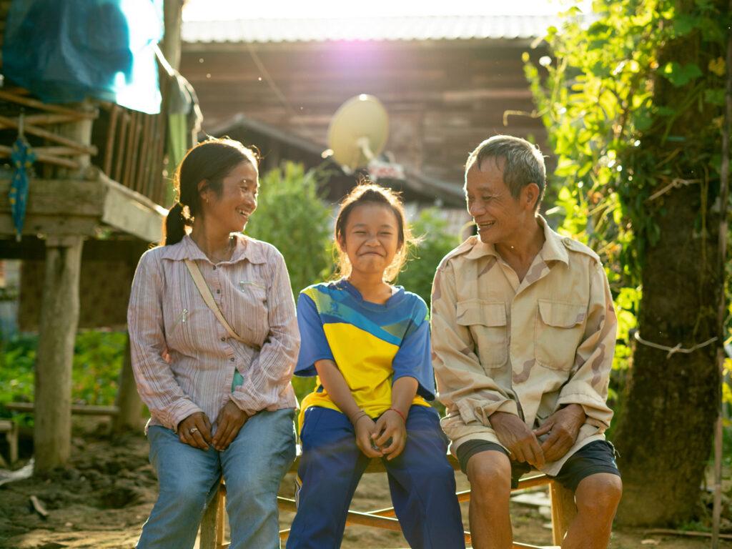En mamma, ett barn och en pappa sitter tillsammans. Bakom dom syns låga byggnader och träd.