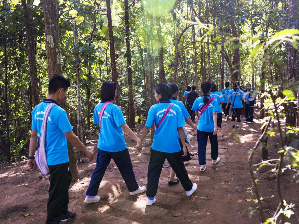Flera människor i likadana ljusblåa t-shirts med text på ryggen går genom ett skogsområde, några håller varandra i handen.