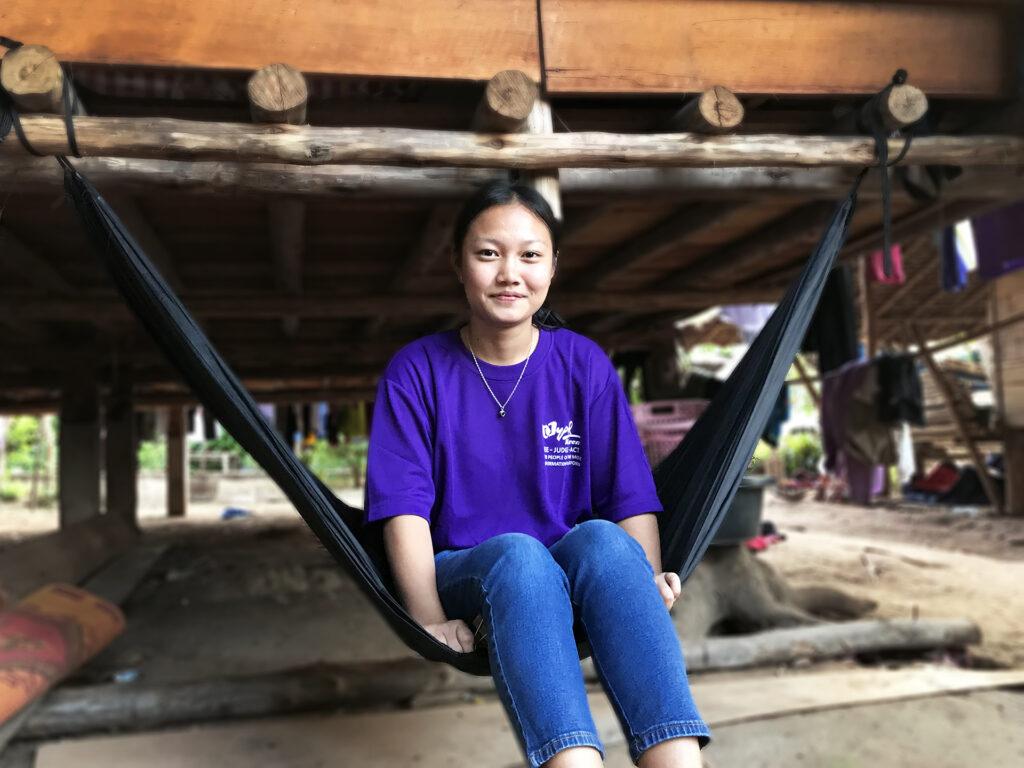 Ung kvinna i lila t-shirt och jeans sitter i en hängmatta. Bakom henne syns en grunden av en byggnad.